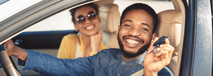 Image of a young African American couple in a new car